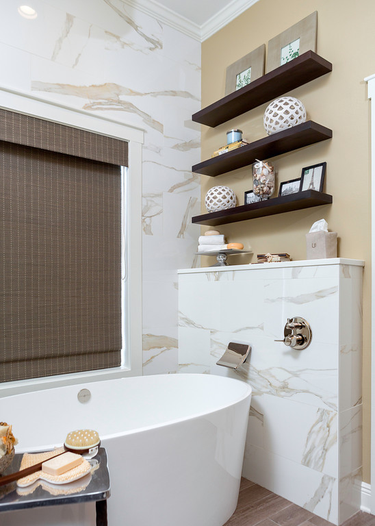 Master bathroom remodel with sophisticated style: marble style tile, horizontal lines, floating shelves