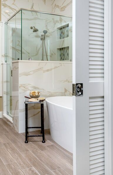 Master bathroom remodel with sophisticated style: marble style tile, glass shower, free standing tub