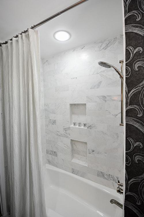 Black and white bath remodel with calcutta oro marble