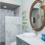 Coastal new construction bathroom, tile shower, blue vanity, porthole mirror, colorful fish details