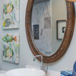 Budget bath with nautical theme, porthole mirror, and colorful fish accents