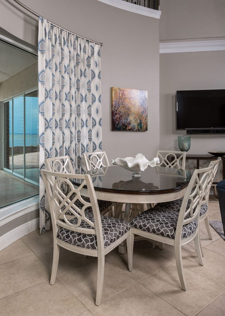 Living space for a busy family, dining area, round table, grerys, blues, and sand tones