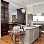 Coastal casual kitchen in waterfront home: Luna Bella jelly fish pendants, grey cabinets, exposed brick, two toned counters, kitchen island, storage