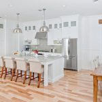 all white kitchen with stainless pendant lights and wood accents