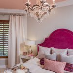 bedroom with hot pink upholstered headboard crystal cahndelier