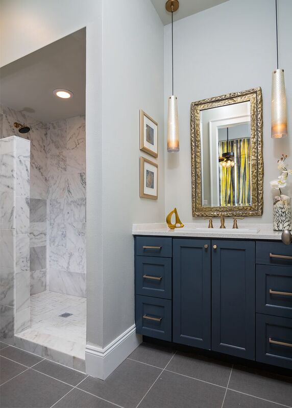 Budget bath with dark blue vanity, gold accent, marble style tiled shower, and pendant light fixtures