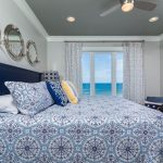 Blue and white nautical bedroom with porthole mirrors and yellow accents