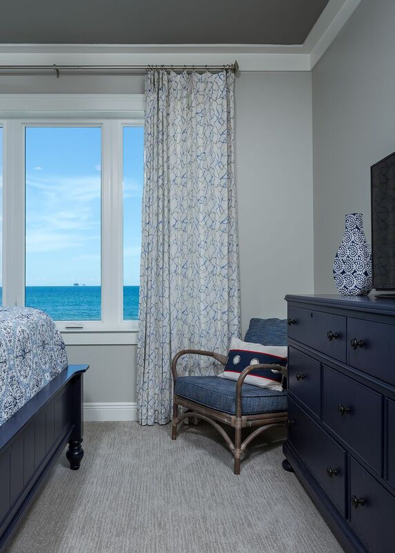 Nautical Bedroom with blue and white bedding, navy dresser, and light colored window treatments