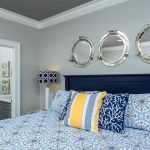 Nautical bedroom with white and blue bedding, yellow accents, and silver porthole mirrors