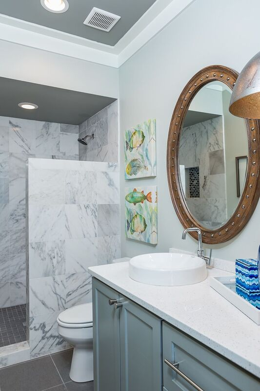 Nautical bathroom with light blue vanity, porthole mirror, tiled shower, and colorful fish accents.