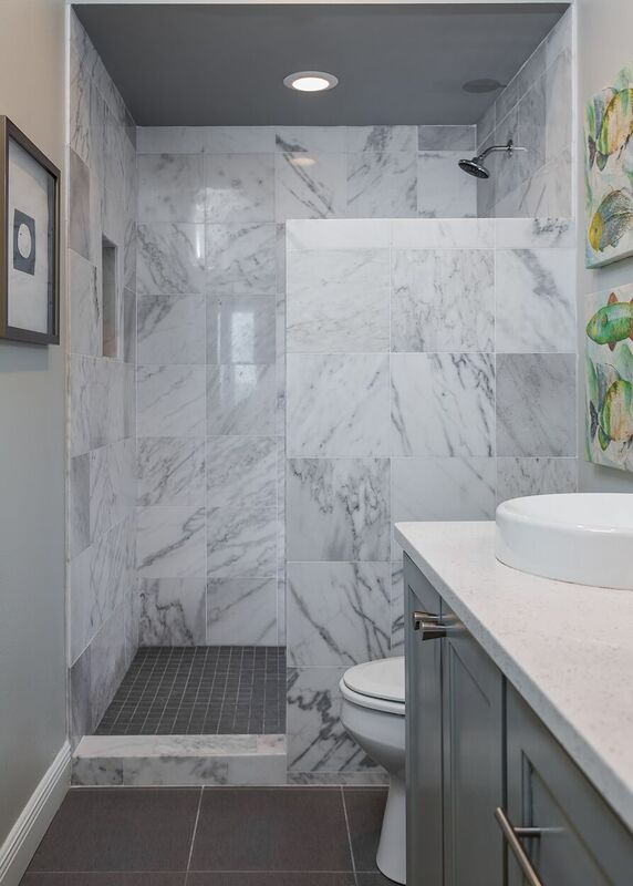 Nautical bathroom with grey and white tiled shower and light blue vanity