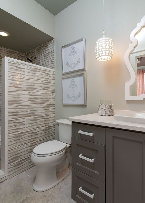 Neutral colored budget bath with grey and white vanity and tiled shower
