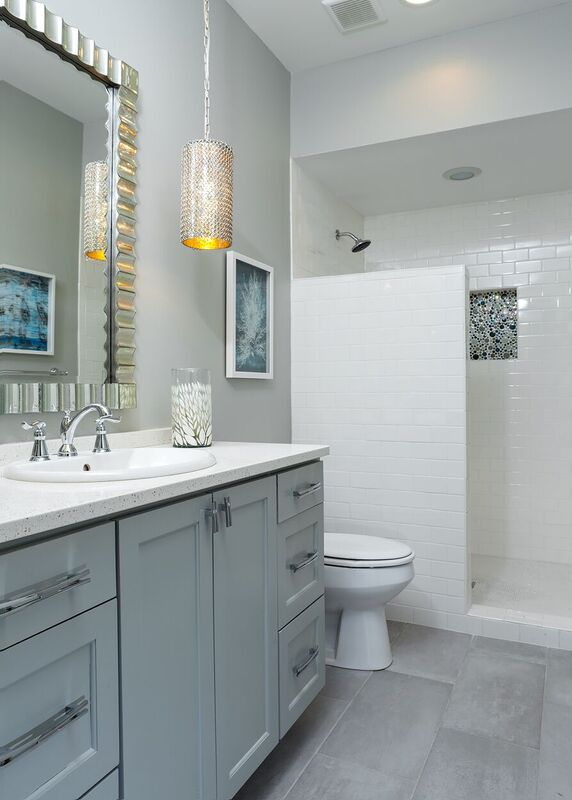 Budget bath with light blue and white vanity, white subway tiled shower, and pendant light fixtures