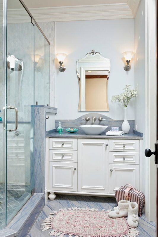 Blue and white bathroom with tile flooring and tiled shower with window