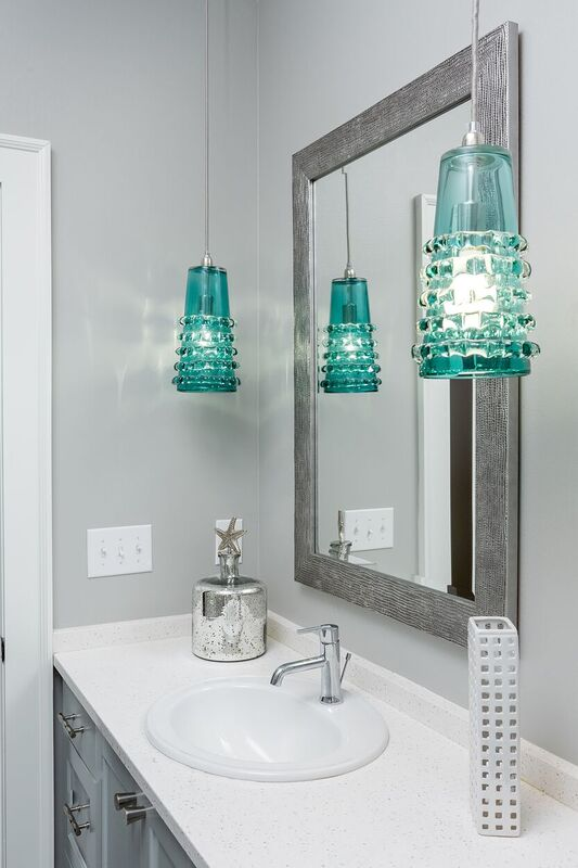 Budget bath with grey walls, light blue and white vanity, and teal pendant light fixtures
