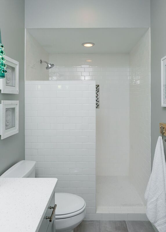 Budget bath with light grey walls and flooring, white subway tiled shower, and teal pendant light fixtures