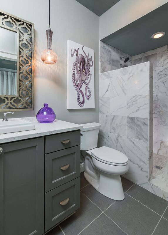Budget bath with grey vanity and tiled shower with purple accents