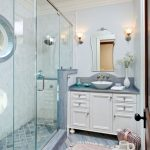 Blue and white bathroom with glass shower with window