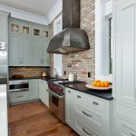 Coastal casual kitchen in waterfront home: grey counters, cold rolled steel hood
