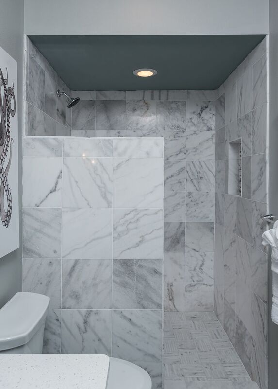 Budget bath with grey marble style tiled shower