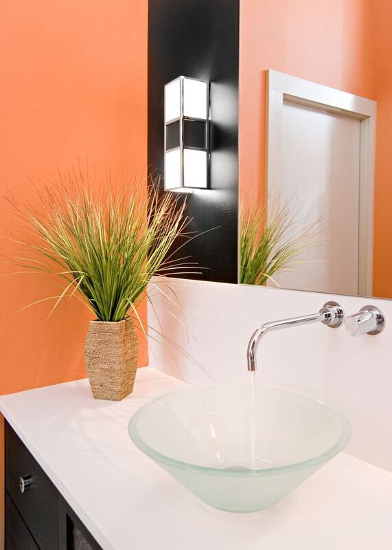 Modern master bath with glass sink, large counter top, and orange walls