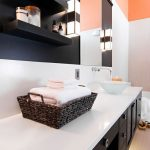 Warm modern master bath with large counter top, glass sink, and orange walls