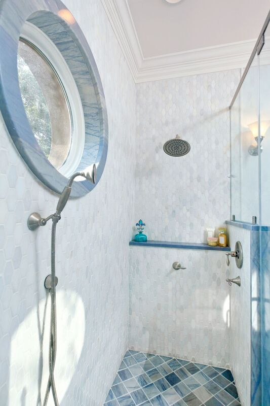 Blue and white tiled shower with window, shelf, and glass door