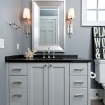 bathroom with grey cabinets and walls stainless sconces and black countertop