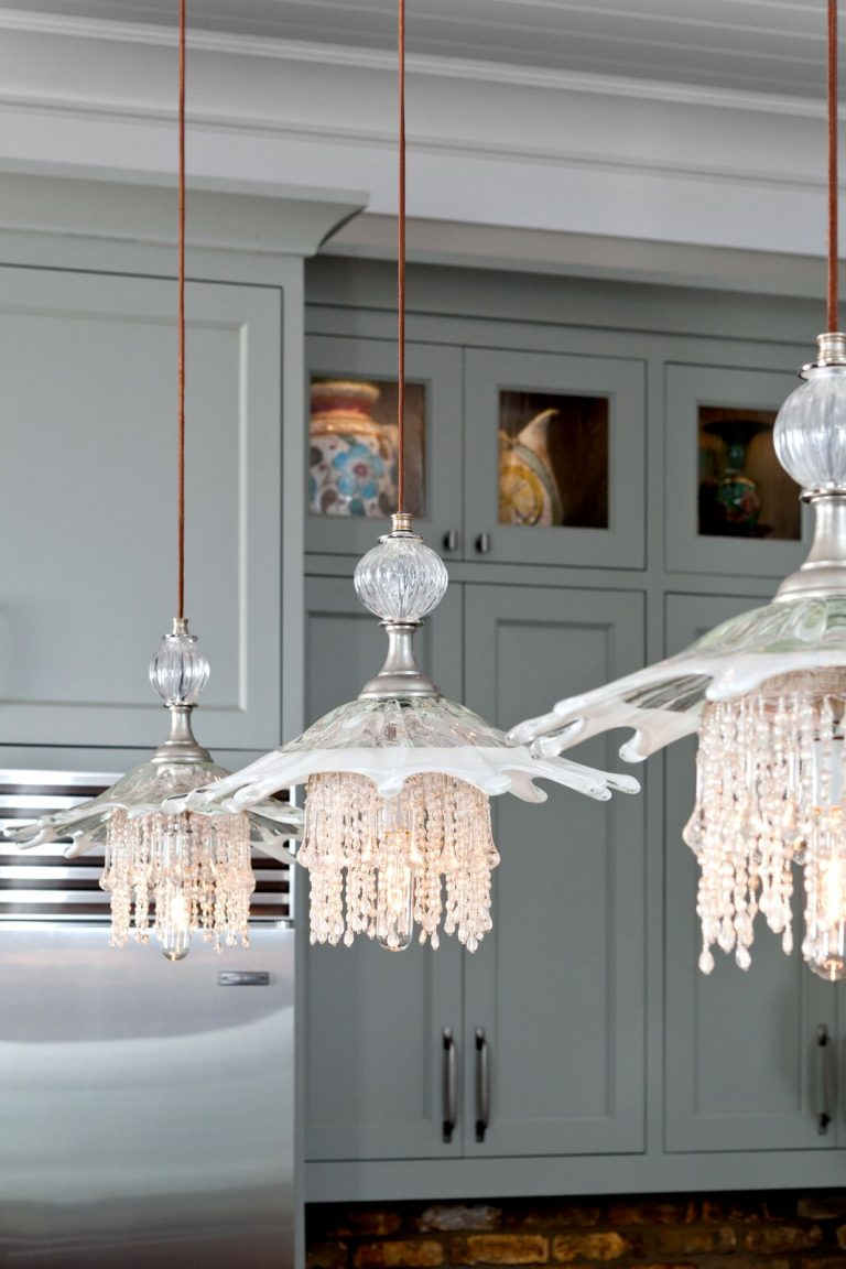 Coastal casual kitchen in waterfront home: Luna Bella jelly fish pendants, grey cabinets, exposed brick