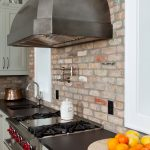 Coastal casual kitchen in waterfront home: grey cabinets, exposed brick, cold rolled steel hood