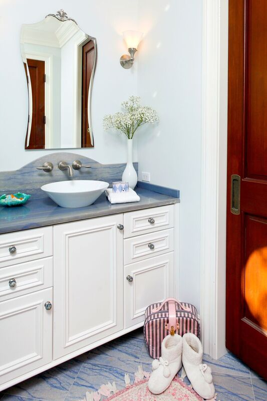 White and blue bathroom with blue counter top and blue tile flooring