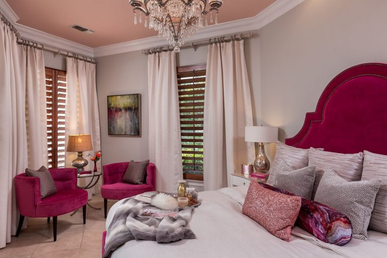 hot pink bedroom with velvet headboard and velvet side chairs crystal chandelier