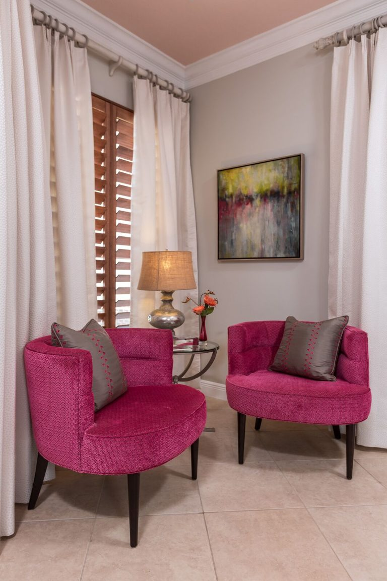 pair of hot pink velvet chairs with abstract painting