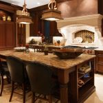Elegant new construction kitchen, kitchen island, knotted cherry cabinetry, Gallo Beach granite, open floor plan, custom hood with stone mantle