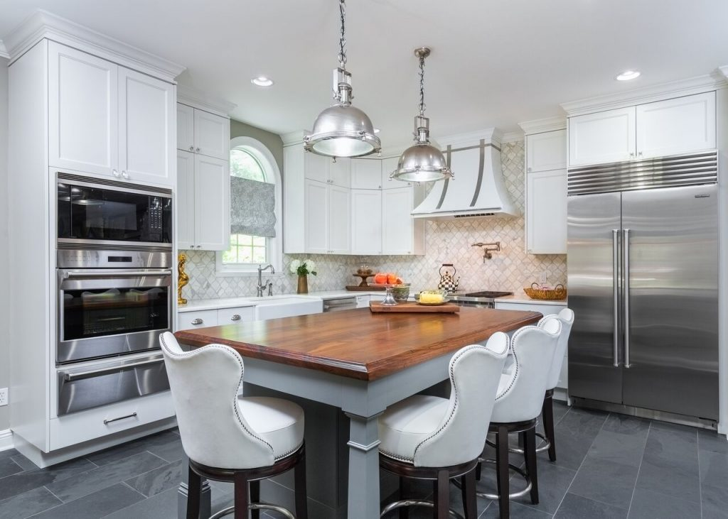 Slate tile, white kitchen cabinets, pendants, grey island, upholstered counter stools, mosaic tile backsplash, roman shade, hood vent, wood top, recessed lighting, stainless appliances