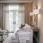 Dark hardwood floors, deep seated sofa, glass coffee table, console table, original artwork, window treatments, lamps
