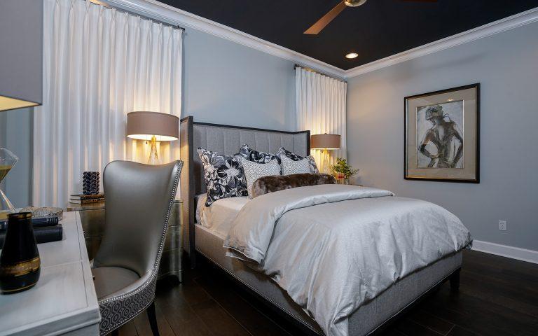 Condo Master bedroom, upholstered bed, dark hardwood floor, upholstered chair, artwork, custom window treatments, custom throw pillows