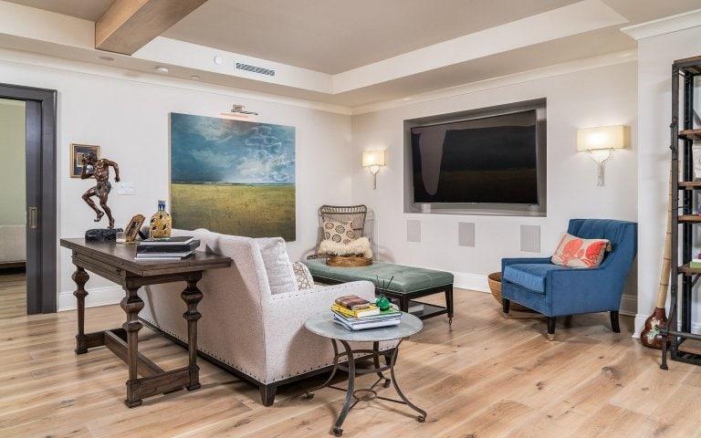 living room with painting light hardwood flooring linen sofa blue velvet chair console art