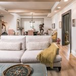Exposed beams with recessed lighting. Deep seated sofa with blue leather ottoman. Accent dining chair with hanging light and original artwork and sculptures.