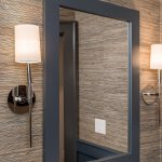 Textured wallcoverings with grey mirror and silver sconces.