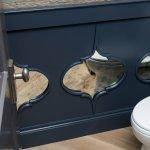 Custom Blue mirrored waincoting, grasscloth wallcoverings, hardwood flooring.