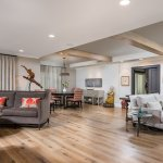 Open concept living room and dining room with deep seated upholstered sofas, custom accent chairs, hanging light, exposed beams and original art.