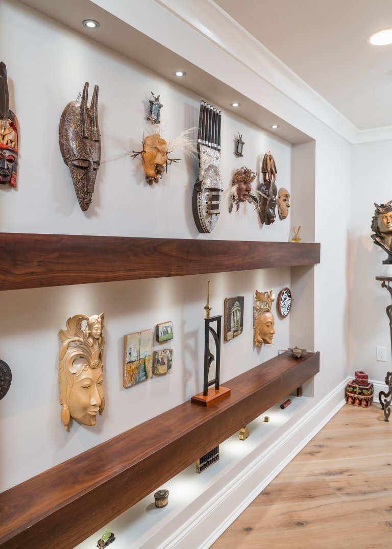 Inset wall with floating shelves and display lighting for original artwork and sculptures.