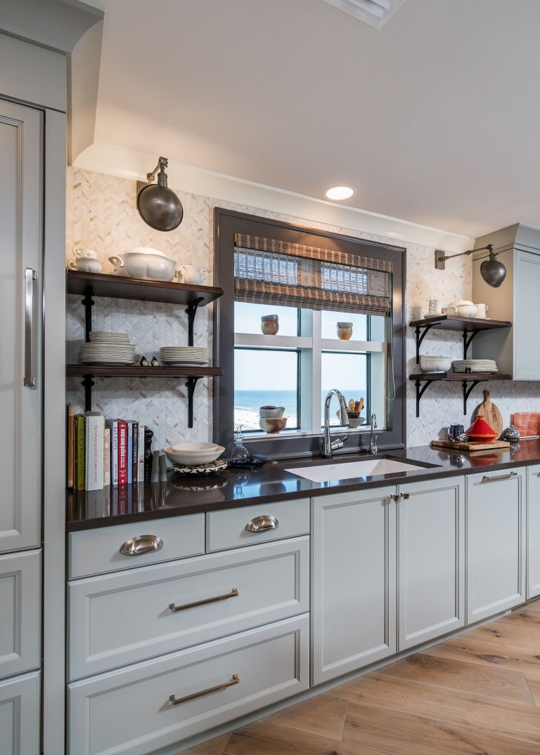 Smoke blue cabinetry with nickel toned hardware. Earth toned countertop with open shelves and sconces.