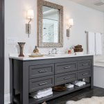 Custom grey vanity with bottom shelf, nickel hardware and marble countertop. Brass mirror with two sconces.