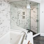 Walk in marble shower with bench and mosaic tile niches connected to an infinity tub.