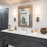 Custom grey Vanity with open bottom shelf, marble countertops with brass mirror and metal sconces.