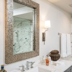 Grey vanity with marble counter top. Brass mirror and metal wall sconce.