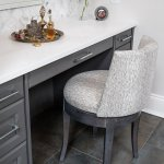 Grey vanity with marble top, mosaic marble tiled wall, custom upholstered chair and two toned tile flooring.