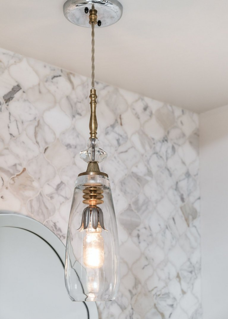 Mosaic marble tile with vanity mirror and hanging artisan lighting.